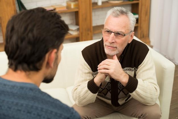 Cara jovem e homem envelhecido no sofá na sala