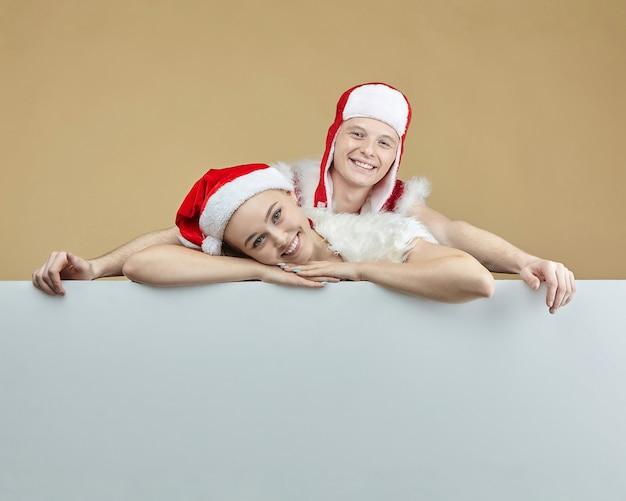 Cara jovem e uma garota em trajes de papai noel em um layout de publicidade. conceito de natal e ano novo