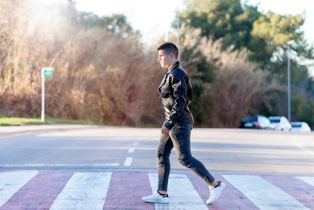Cara jovem elegante em roupas causais, caminhando ao longo da faixa de pedestres da cidade.