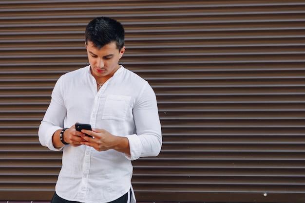 Cara jovem elegante na camisa digitando no telefone no fundo simples