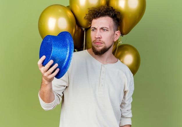 Cara jovem eslavo bonito carrancudo em pé na frente de balões segurando e olhando para o chapéu de festa isolado em um fundo verde oliva com espaço de cópia