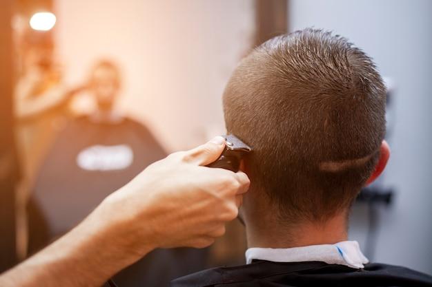 Cara jovem faz um corte de cabelo curto em uma barbearia com um aparador, close-up