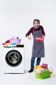 Cara jovem feliz de vista frontal com avental segurando uma placa de venda em pé perto da máquina de lavar no fundo branco