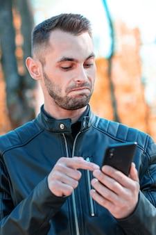 Cara jovem ficou surpreso com o smartphone preto no belo parque de outono. jovem bonito com telefone celular em dia de sol - retrato em close-up médio