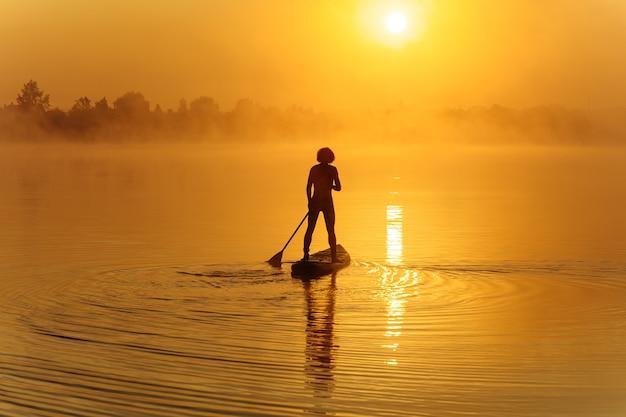 Cara jovem forte em calção de banho, usando remo para flutuar no supboard durante o tempo da manhã.
