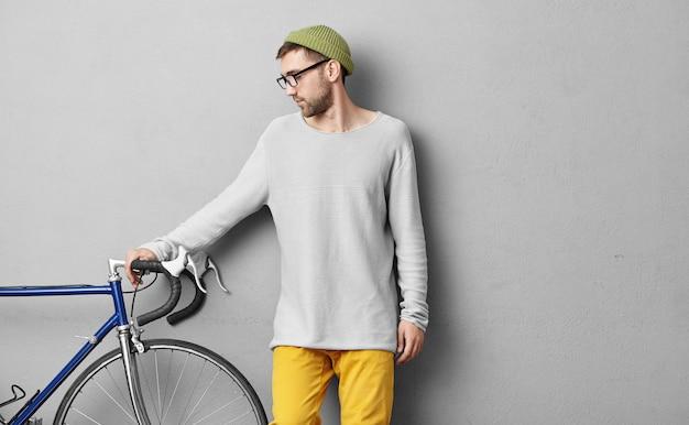 Cara jovem hippie de blusa solta e óculos, escolhendo a bicicleta para si mesmo, quer se exercitar todos os dias e fazer longas viagens ao ar livre, olhando para a bicicleta moderna, mantendo a mão no guidão