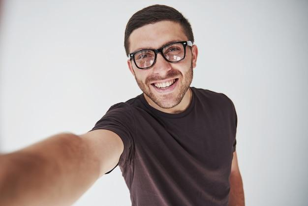 Cara jovem hippie de óculos rindo alegremente isolado no branco
