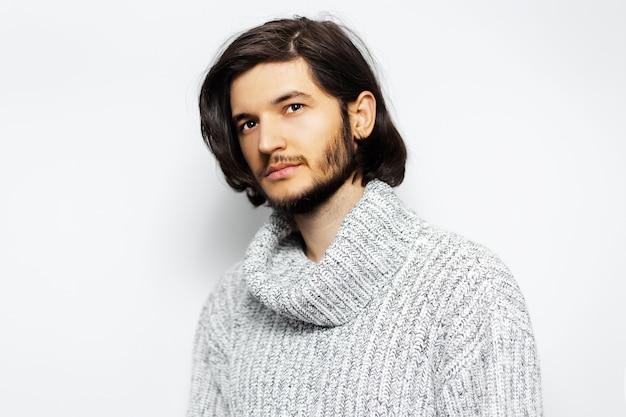 Cara jovem jurando suéter de gola alta na parede branca.