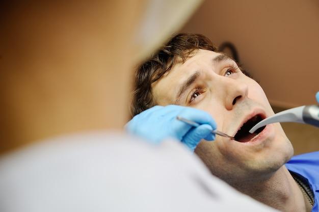 Cara jovem no consultório odontológico. medo dos dentistas