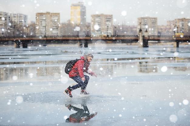 Cara jovem patinando em uma pista de gelo da cidade em uma lagoa congelada