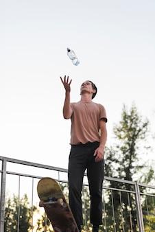 Cara jovem posando com skate e garrafa de água