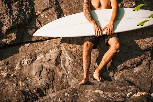Cara jovem, segurando a prancha de surf perto de pedras