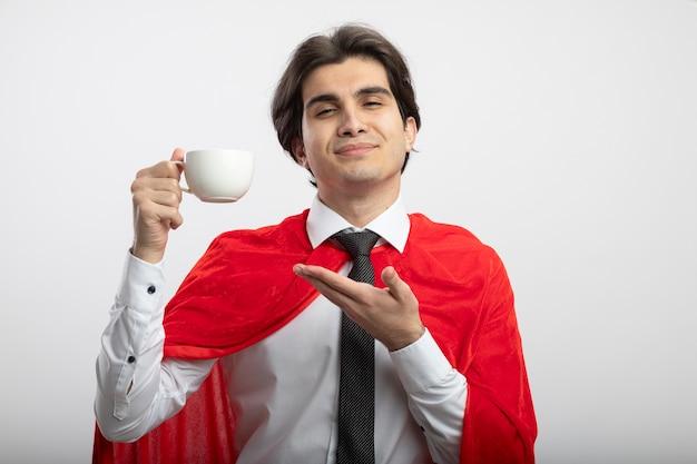 Cara jovem super-herói satisfeito usando gravata segurando e aponta com a mão na xícara de café isolado no fundo branco