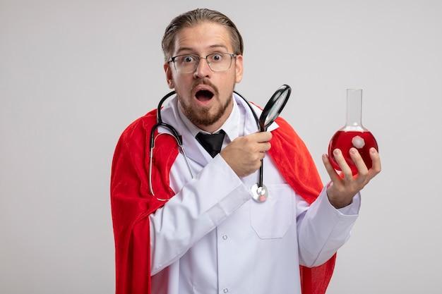 Cara jovem super-herói surpreso vestindo túnica médica com estetoscópio e óculos segurando uma garrafa de vidro de química cheia de um líquido vermelho e uma lupa isolada no fundo branco