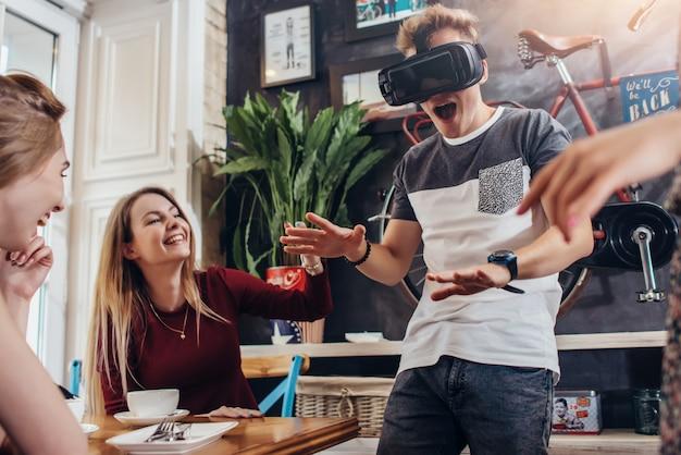 Cara jovem, testando o fone de ouvido de realidade virtual, gritando jogando jogo assustador, enquanto seus amigos alegres rindo dele sentado em um café