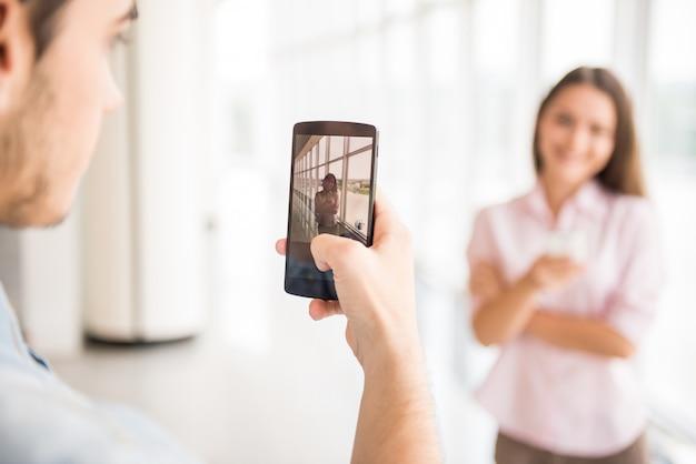 Cara jovem tirando foto de sua namorada bonita dentro de casa.
