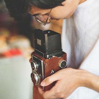 Cara jovem, tirando fotos com uma câmera vintage