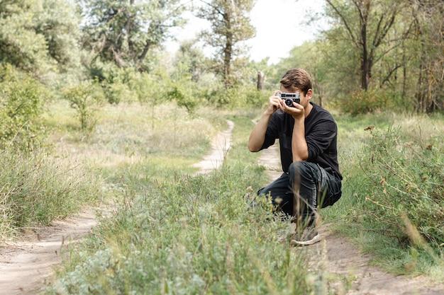 Cara jovem, tirando fotos na natureza com cópia-espaço