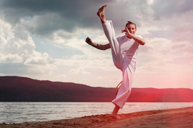 Cara jovem treina capoeira