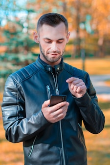 Cara jovem usando smartphone preto no belo parque de outono. jovem bonito com telefone celular em dia de sol - retrato de plano médio