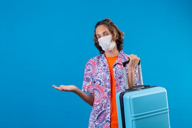 Cara jovem viajante usando máscara protetora facial, segurando a mala de viagem sem noção e confuso em pé com o braço levantado