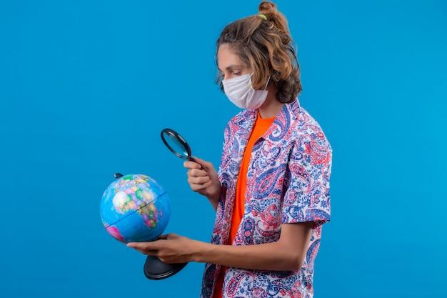 Cara jovem viajante usando máscara protetora facial segurando uma mala de viagem segurando e olhando através de uma lupa no globo com interesse em pé sobre o fundo azul