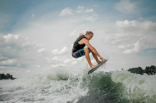 Cara jovem, wakesurfing no quadro rio abaixo