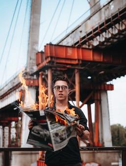 Cara lê um jornal em chamas