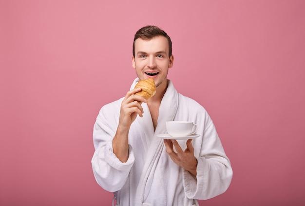 Cara legal alegre em roupão branco está de pé na parede de volta com croissant perfumado