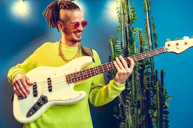 Cara legal com dreads praticando guitarra em casa