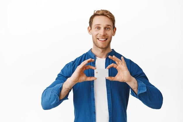 Cara legal e bonito sorrindo e mostrando seu cartão de crédito do banco, cliente platina, em pé contra uma parede branca em roupas casuais