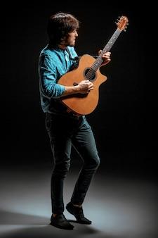 Cara legal em pé com guitarra no escuro