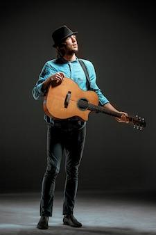 Cara legal em pé com o violão na parede escura