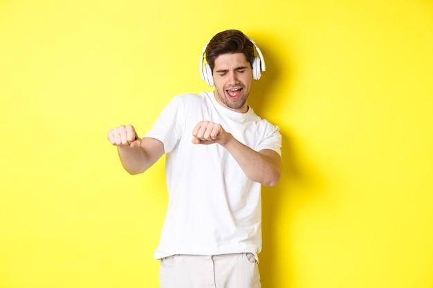 Cara legal ouvindo música em fones de ouvido e dançando, em pé com roupas brancas contra a parede amarela do estúdio