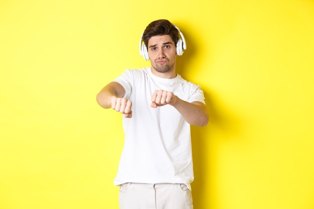 Cara legal ouvindo música em fones de ouvido e dançando, em pé com roupas brancas contra o fundo amarelo do estúdio.