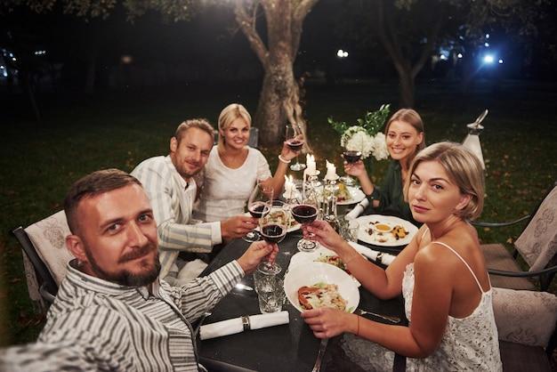 Cara leva selfie. grupo de amigos no desgaste elegante jantar de luxo