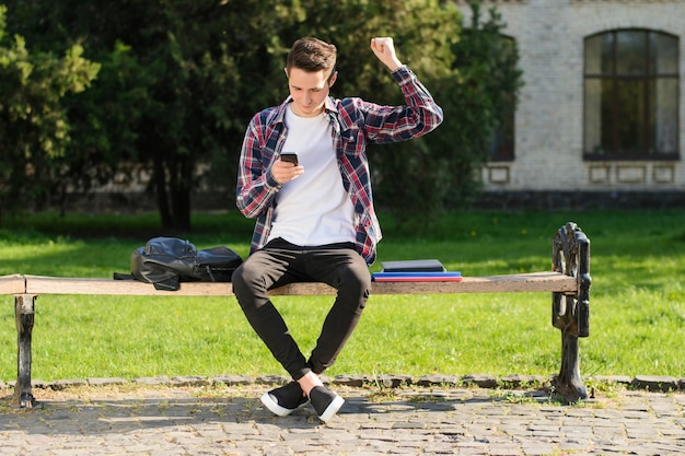 Cara levantando o punho segurando um telefone sentado no banco
