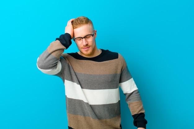 Cara loiro com um suéter rindo e batendo na testa