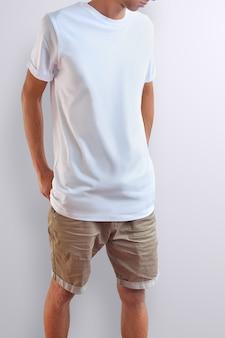 Cara magro atraente em uma camiseta em branco e shorts marrom de algodão em um fundo branco do estúdio. pose frontal. o maquete pode ser usado em sua vitrine.