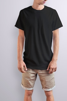 Cara magro elegante em uma camiseta preta e shorts marrom de algodão em um fundo branco do estúdio. pose frontal. o maquete pode ser usado em sua vitrine.