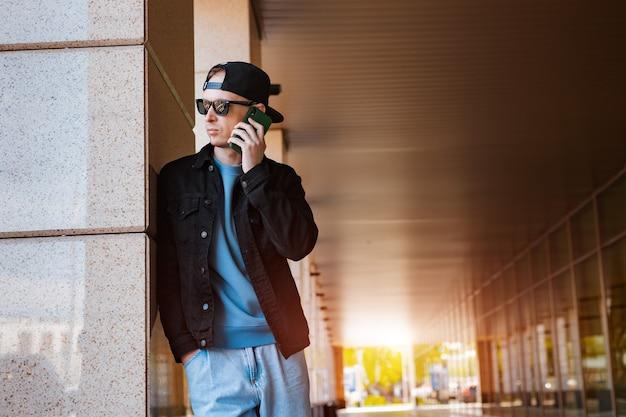Cara milenar hippie em roupa elegante, em pé ao ar livre, falando em um smartphone