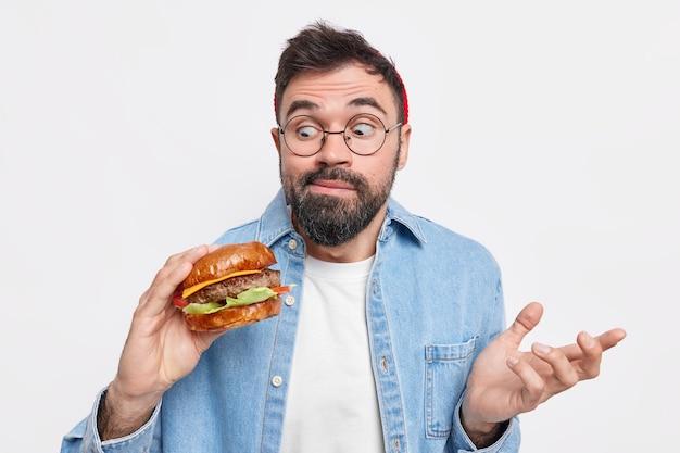 Cara milenar surpreso olha com grande apetite para hambúrguer fresco come fast food não se preocupa com nutrição usa óculos, camisa jeans posa contra a parede branca. conceito de comer demais.
