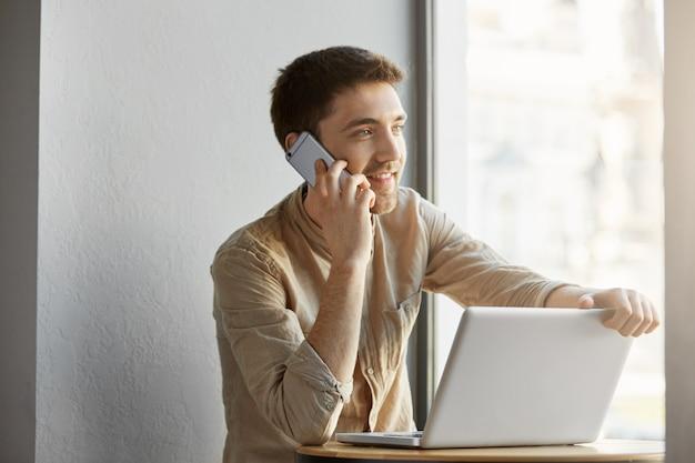 Cara morena bonito alegre com olhos cinzentos, trabalhando no refeitório no computador portátil, sorrindo e falando no telefone com o cliente sobre detalhes do pedido.