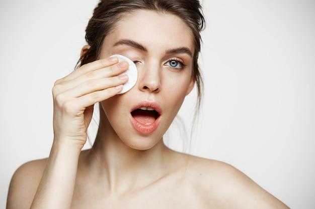 Cara moreno natural bonita bonito da limpeza da menina com esponja do algodão que sorri olhando a câmera sobre o fundo branco. cosmetologia e spa.