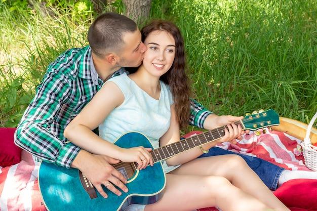 Cara mostra a garota como tocar violão