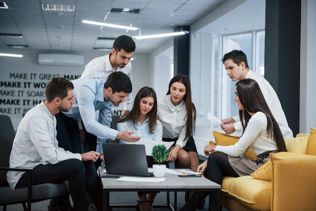 Cara mostra o documento para uma garota. grupo de jovens freelancers no escritório tem conversa e trabalhando