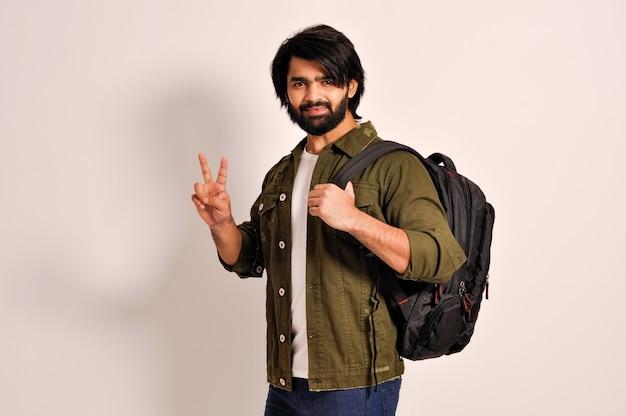 Cara mostrando dois dedos fazendo sinal de vitória segurando uma mochila