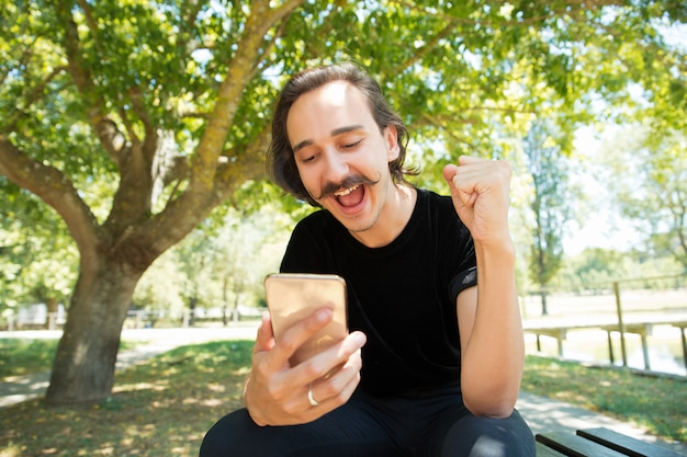 Cara muito feliz animado com telefone inteligente, regozijando-se com boas notícias