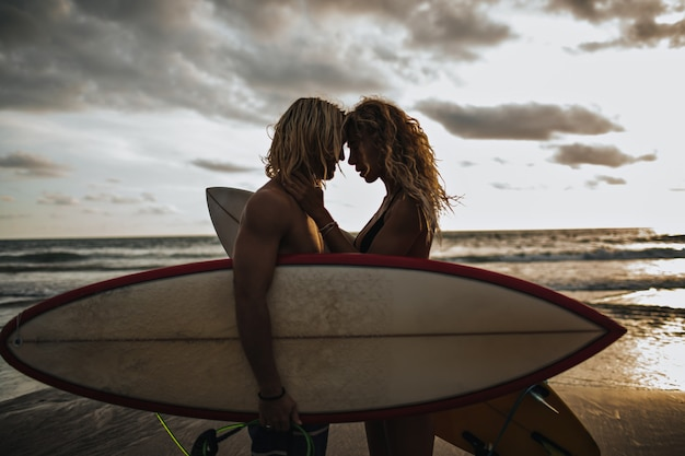 Cara musculoso e sua garota magra se divertem. casal posando com pranchas de surf