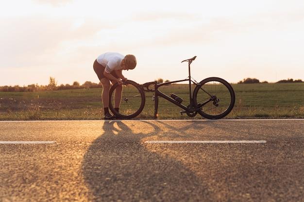 Cara musculoso em roupas esportivas e capacete protetor consertando roda de bicicleta ao ar livre